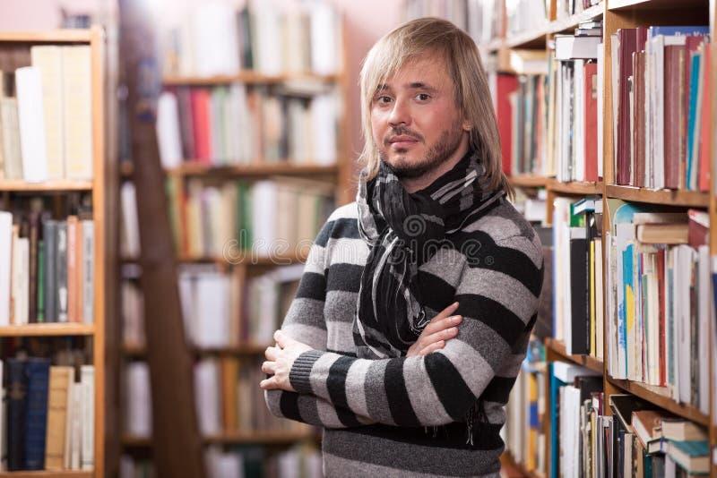 Homem considerável que olha a câmera ao estar no corredor na biblioteca fotografia de stock