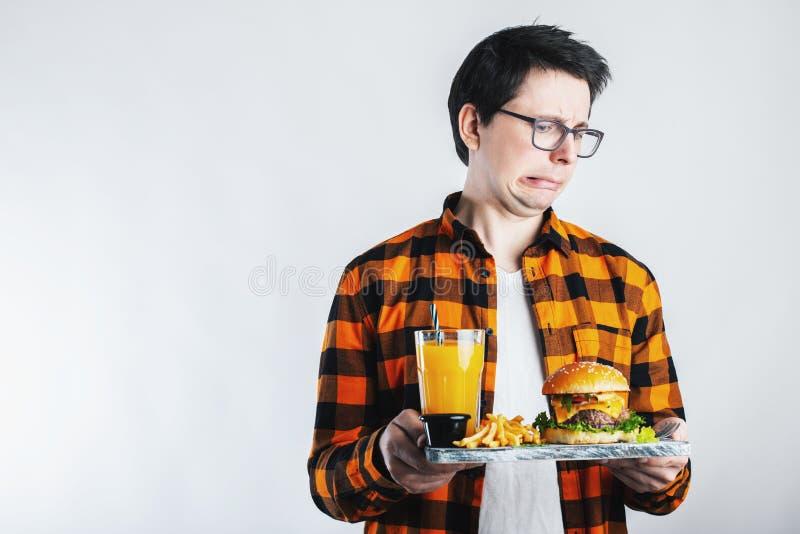Homem considerável que recusa o hamburguer insalubre contra o fundo branco Faça dieta o conceito Com espaço da cópia para o texto imagem de stock