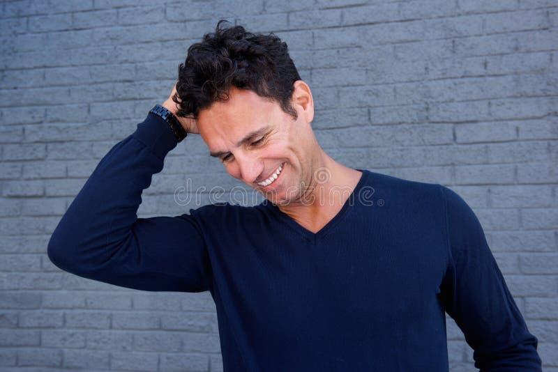 Homem considerável que ri com mão no cabelo contra a parede cinzenta fotos de stock