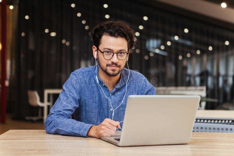 Homem considerável que senta-se na tabela com o portátil no escritório foto de stock royalty free