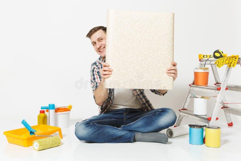Homem considerável que senta-se no assoalho com rolo desdobrado de instrumentos do papel de parede para a sala do apartamento da  foto de stock royalty free