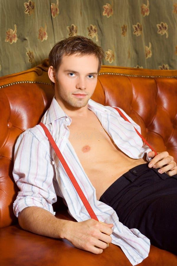 Homem considerável que senta-se no sofá imagem de stock royalty free