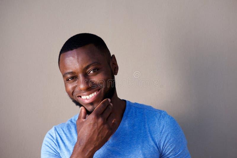 Homem considerável que sorri com mão à barba imagem de stock