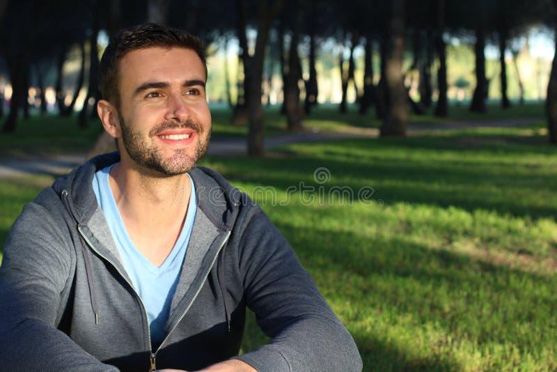 Homem considerável que sorri no parque ao olhar o por do sol ou o nascer do sol foto de stock royalty free