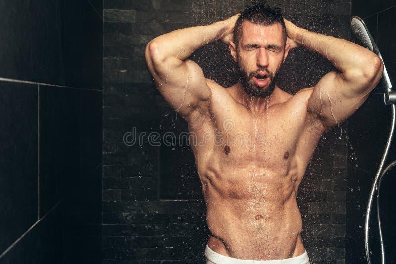 Homem considerável que toma o chuveiro Homem muscular que rega após o exercício fotografia de stock royalty free