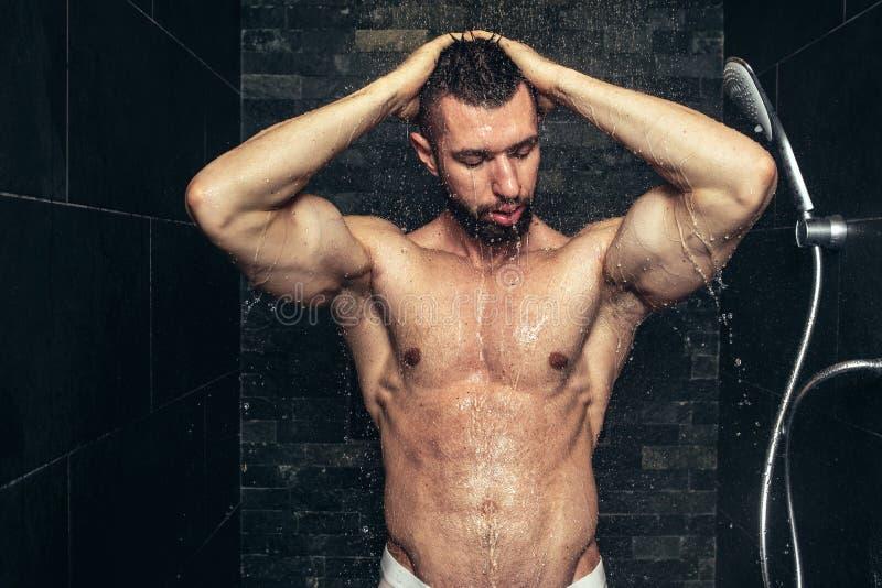 homem considerável que toma um chuveiro na manhã Rega de vista natural do atleta fotografia de stock