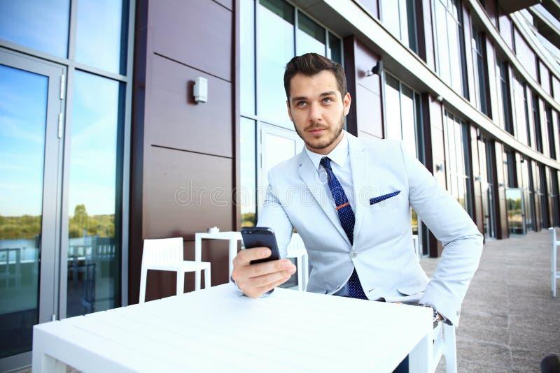 Homem considerável que trabalha com smartphone e originais no café do ar livre fotografia de stock