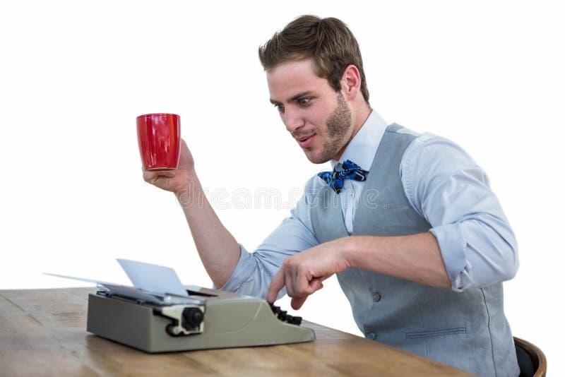 Homem considerável que usa a máquina de escrever antiquado fotografia de stock