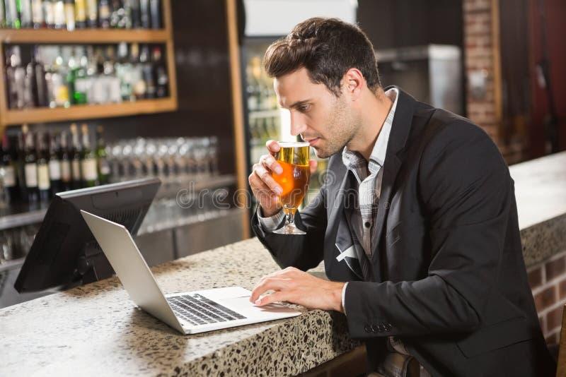 Homem considerável que usa o portátil e comendo uma cerveja imagem de stock