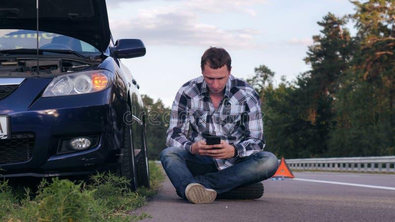 Homem considerável que usa o telefone celular após um acidente de viação fotos de stock
