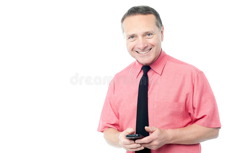 Homem considerável que usa seu smartphone foto de stock