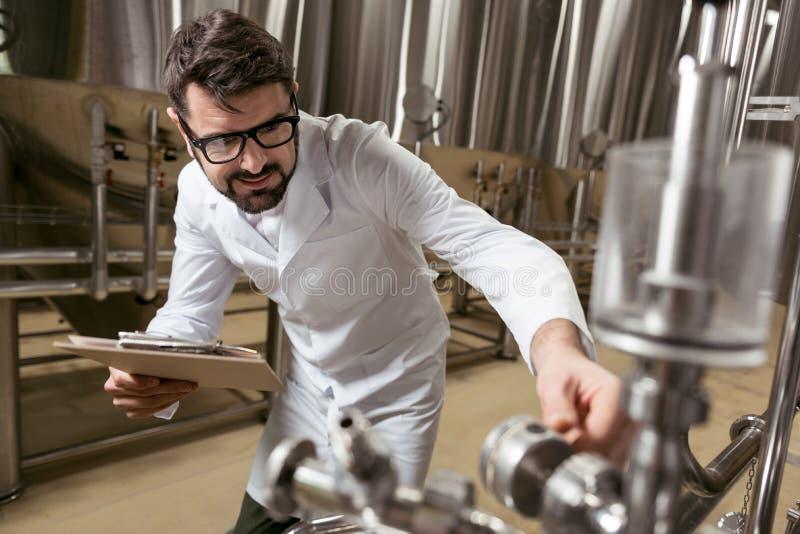 Homem considerável que verifica o mecanismo da fabricação de cerveja fotografia de stock