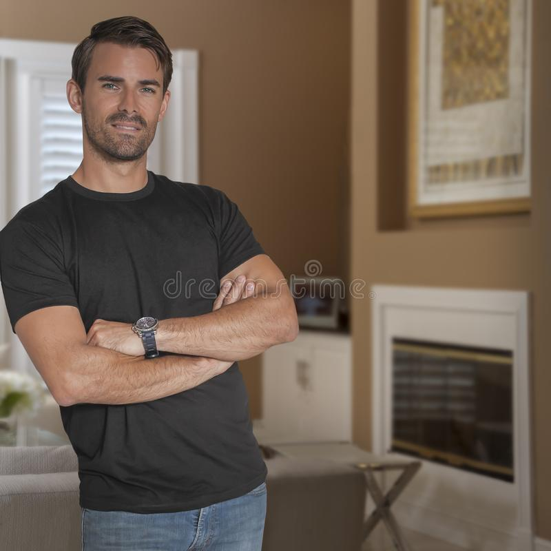 Homem considerável que veste um t-shirt preto e olhares das calças de brim na câmera fotografia de stock
