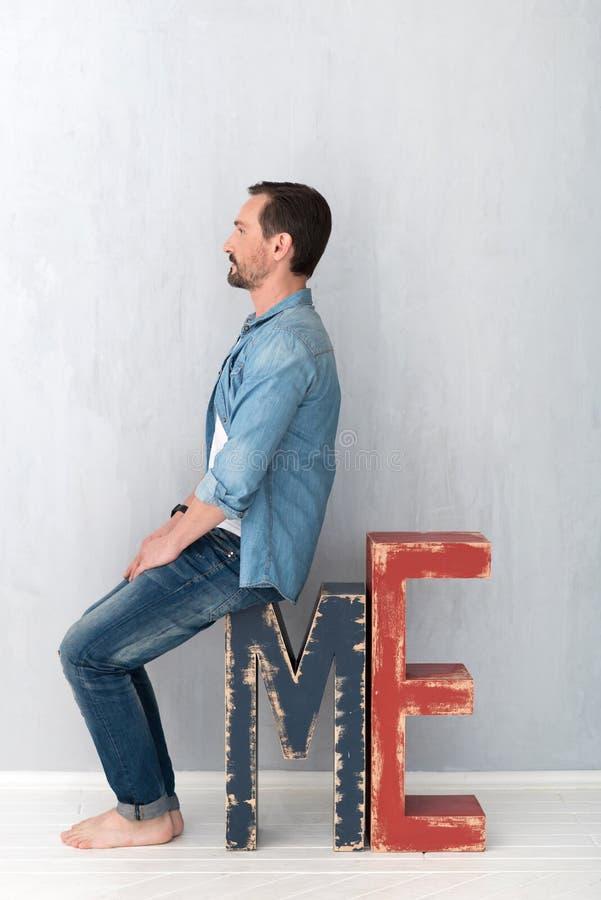 Homem considerável sério que senta-se na grande letra M fotos de stock
