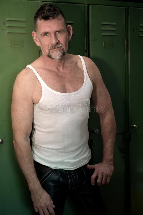 Homem consider?vel em seu 50s com o t-shirt rasgado branco fotos de stock royalty free