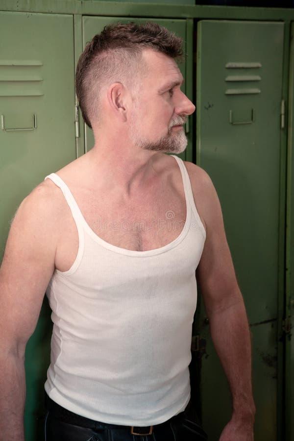 Homem consider?vel em seu 50s com o t-shirt rasgado branco imagem de stock royalty free