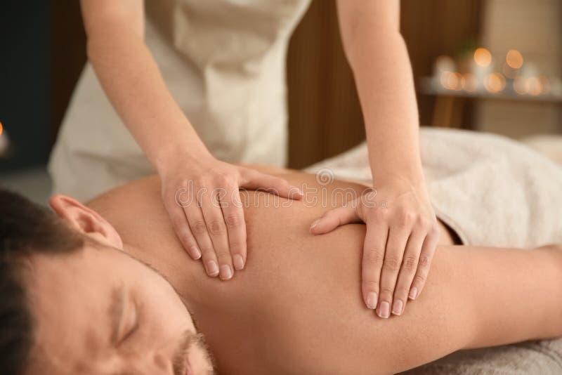 Homem consider?vel que recebe a massagem traseira no sal?o de beleza dos termas fotos de stock royalty free