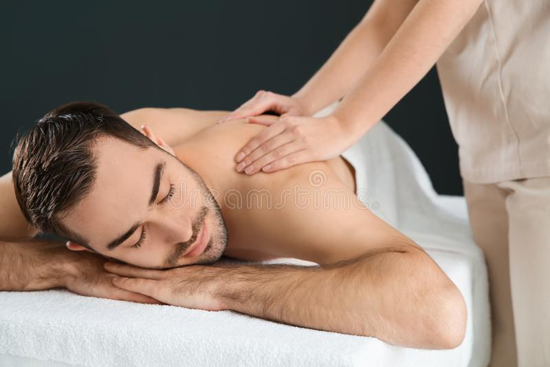 Homem consider?vel que recebe a massagem traseira Servi?o dos termas imagem de stock