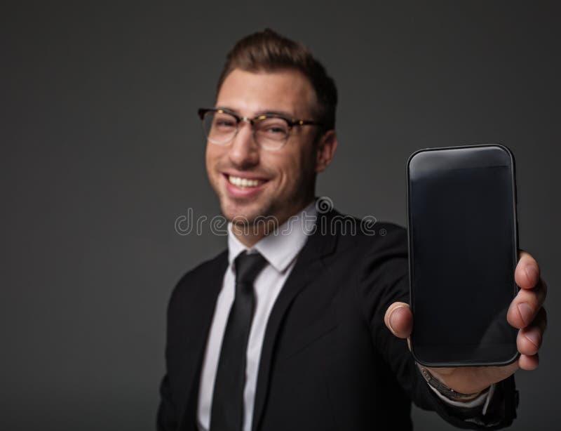 Homem contente que guarda o telefone no braço imagens de stock
