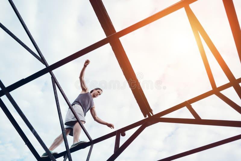 Homem corajoso novo que equilibra na parte superior da ponte do metal alto fotografia de stock