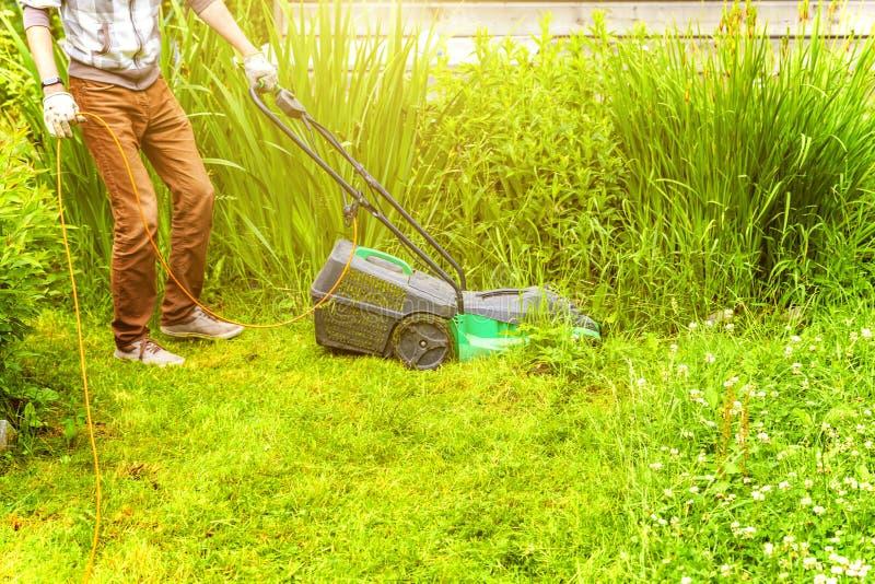 Homem cortando grama verde com cortador de grama no quintal Estilo de vida do campo de jardinagem Linda vista sobre a grama verde fotos de stock royalty free