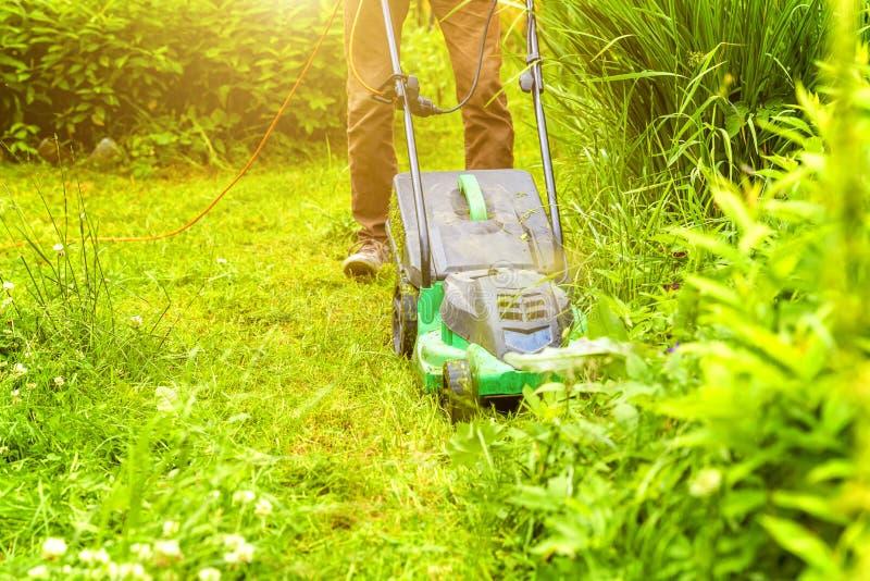 Homem cortando grama verde com cortador de grama no quintal Estilo de vida do campo de jardinagem Linda vista sobre a grama verde imagens de stock