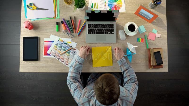 Homem criativo que faz guindastes do origâmi para acalmar-se para baixo, meditando sobre ideias, vista superior imagem de stock royalty free