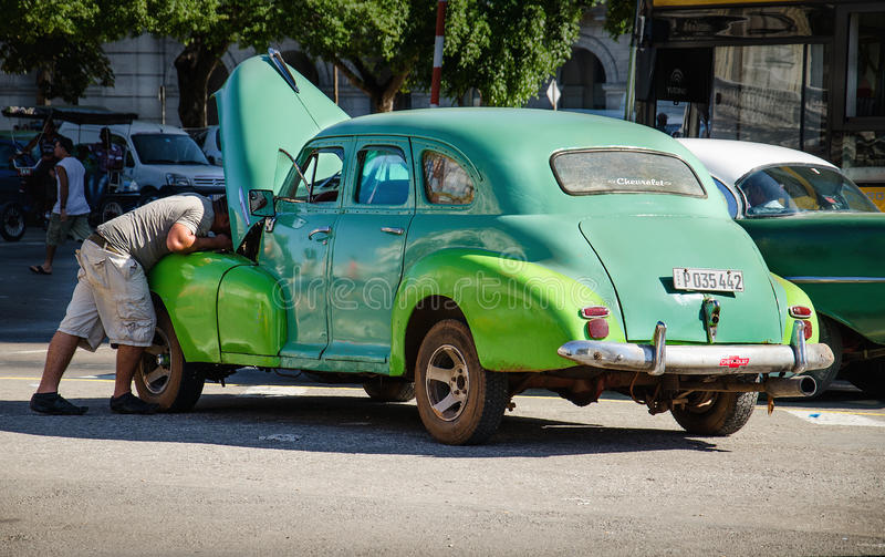 Homem cubano que repara o carro americano clássico quebrado em ruas de Havana imagem de stock royalty free