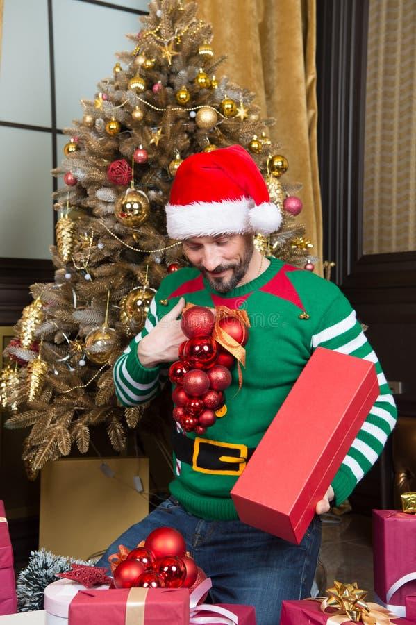 Homem cuidadoso no traje do duende que olha bolas e sorriso do ornamento fotos de stock