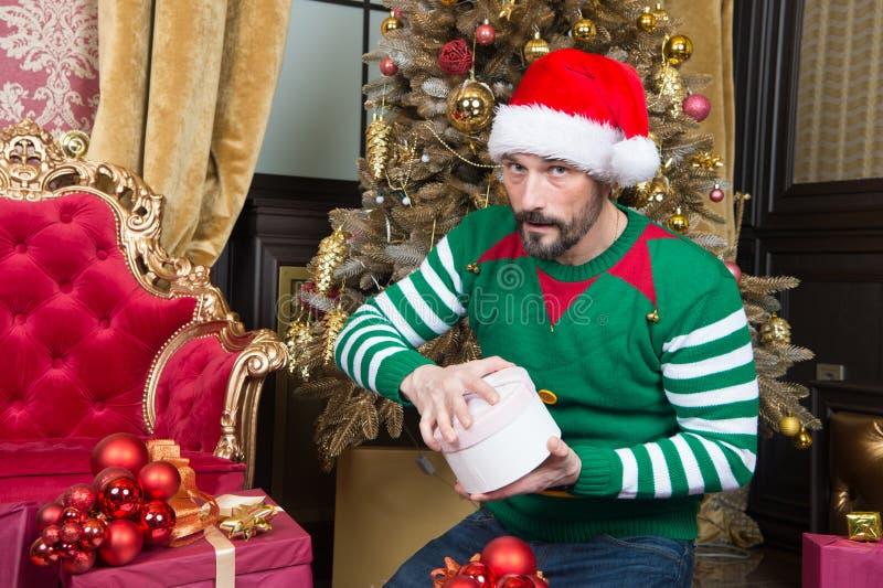 Homem cuidadoso que abre a caixa de presente e que olha o fotos de stock royalty free