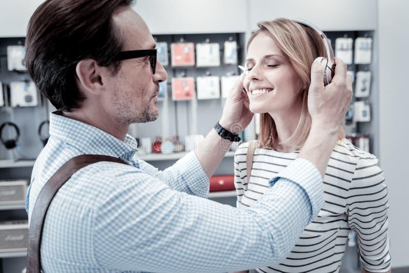 Homem cuidadoso que dá fones de ouvido a seu amigo fotos de stock
