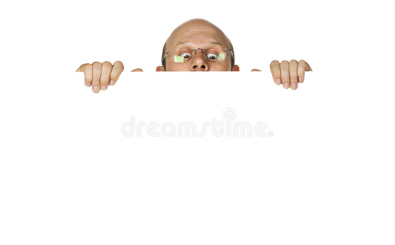 Homem curioso que olha sobre o wallsign branco. fotografia de stock royalty free