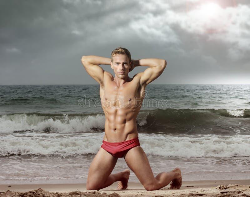 Homem da aptidão na praia foto de stock