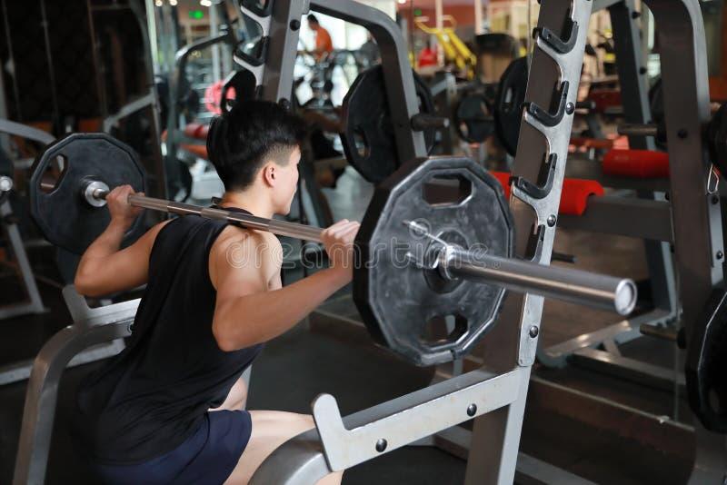 Homem da aptidão no gym que faz a ocupa Homem com ginástica do equipamento de treinamento do peso do dumbbell Interno, instrutor imagens de stock