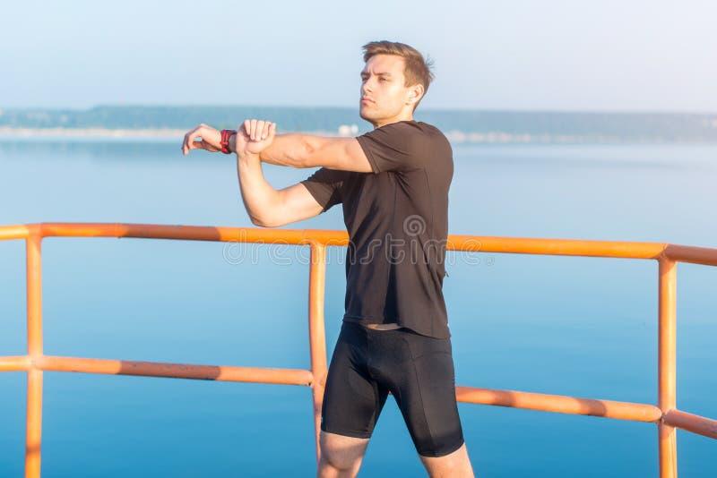 Homem da aptidão que estica os braços, ombro Corredor que aquece-se e que exercita imagens de stock