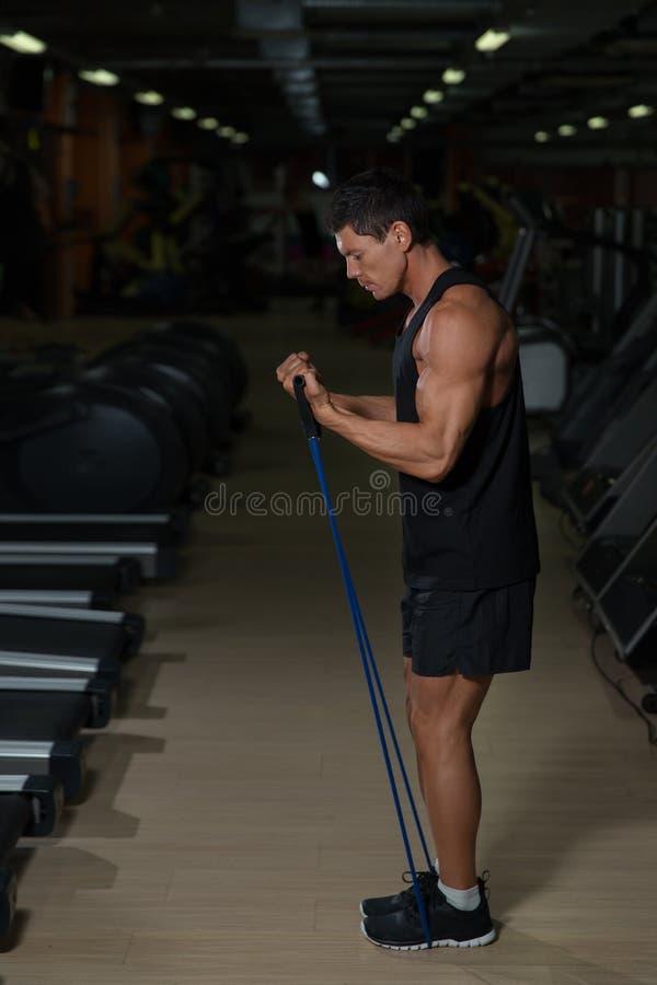 Homem da aptidão que exercita com esticão da faixa no gym Homem muscular dos esportes que exercita com elástico elástico imagem de stock