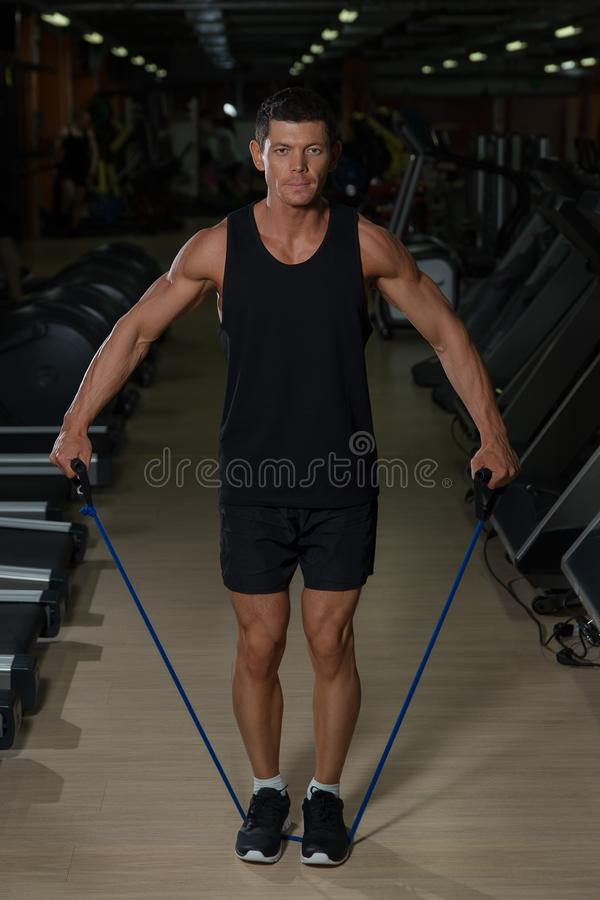 Homem da aptidão que exercita com esticão da faixa no gym Homem muscular dos esportes que exercita com elástico elástico foto de stock