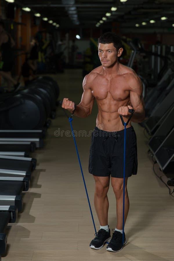 Homem da aptidão que exercita com esticão da faixa no gym Homem muscular dos esportes que exercita com elástico elástico Indivídu fotografia de stock