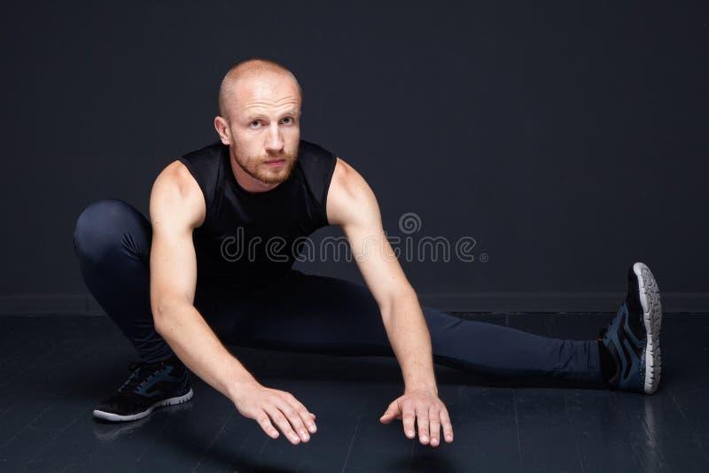 Homem da aptidão que faz esticando exercícios fotos de stock