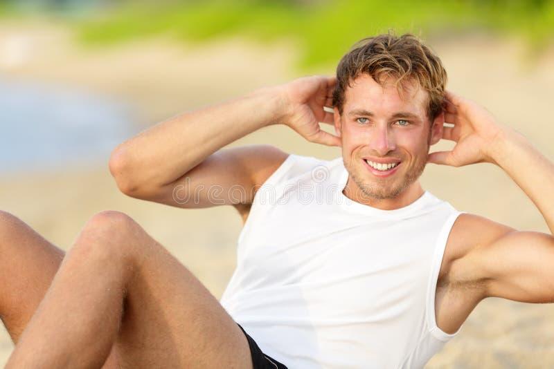Homem da aptidão que faz triturações sentar-UPS na praia imagem de stock royalty free