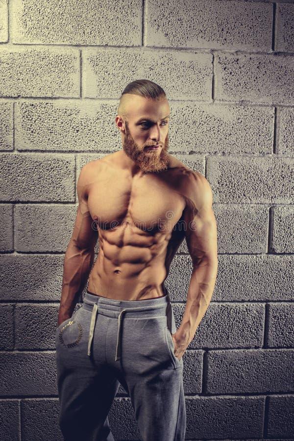 Homem da aptidão que levanta em um clube do gym fotografia de stock