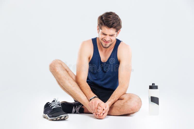 Homem da aptidão que senta-se e que sofre com dor do pé foto de stock