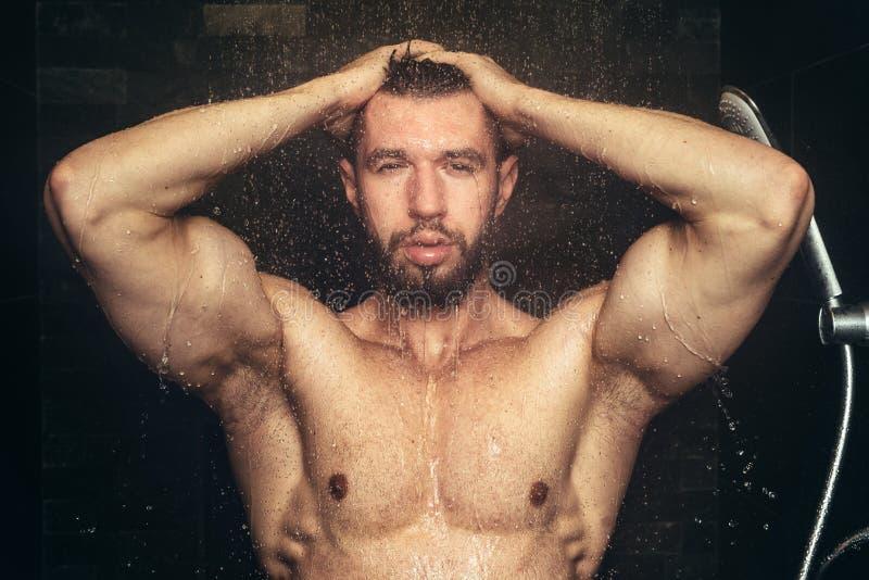 Homem da aptidão que toma um chuveiro e que guarda as mãos na cabeça Feche acima dos detalhes do chuveiro e do banho imagens de stock royalty free