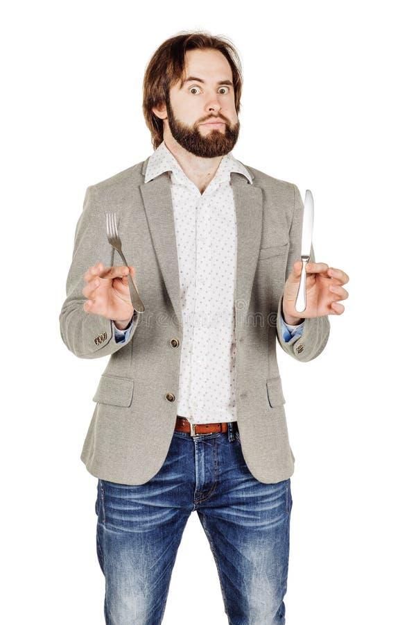 Homem da barba que guarda a forquilha e a faca da cutelaria disponível fotografia de stock royalty free