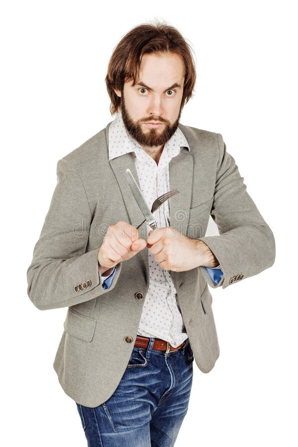 Homem da barba que guarda a forquilha e a faca da cutelaria disponível imagens de stock royalty free