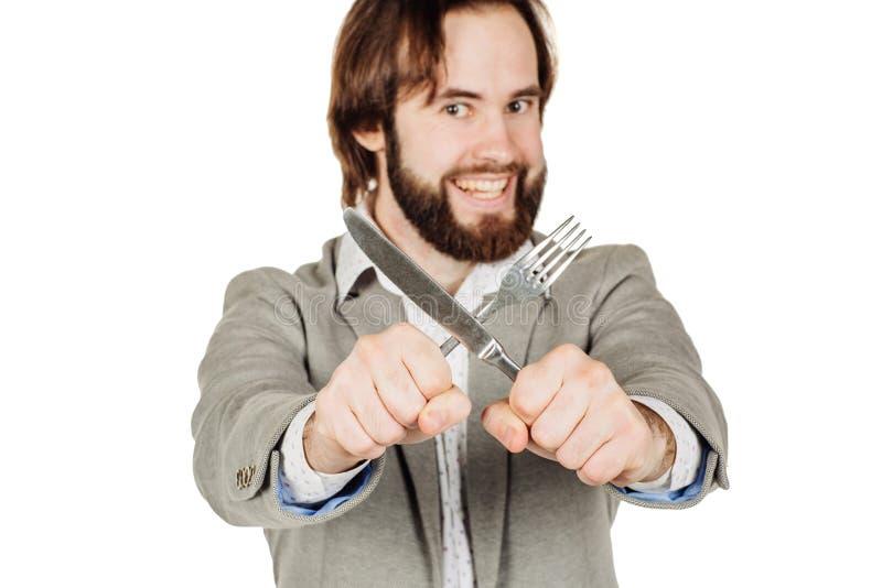 Homem da barba que guarda a forquilha e a faca da cutelaria disponível foto de stock royalty free
