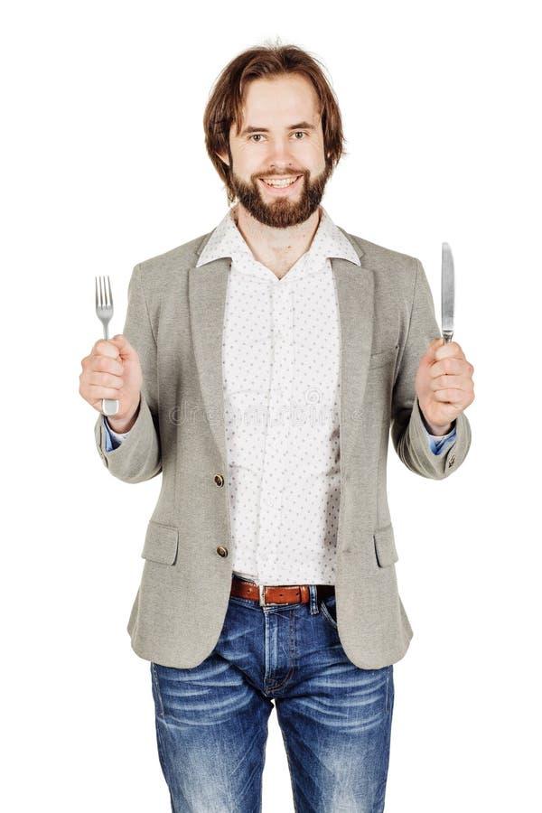 Homem da barba que guarda a forquilha e a faca da cutelaria disponível dieta, alimento, ele foto de stock royalty free