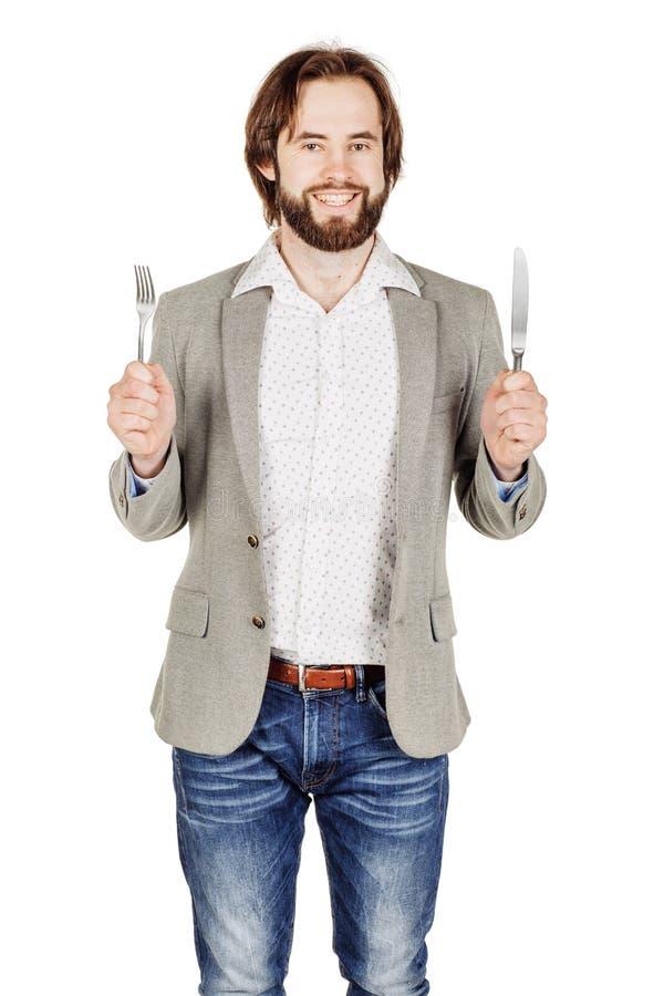 Homem da barba que guarda a forquilha e a faca da cutelaria disponível dieta, alimento, ele foto de stock