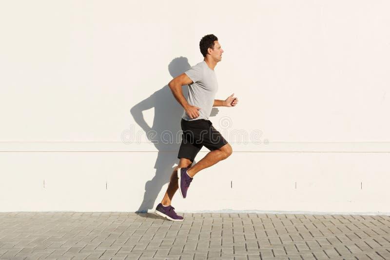 Homem da Idade Média que corre pela parede branca fotografia de stock