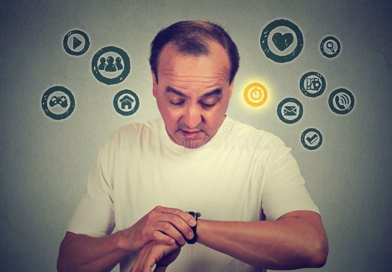 Homem da Idade Média que usa-se verificando o tempo em seu relógio esperto com os ícones dos apps Conceito do dispositivo da nova fotos de stock